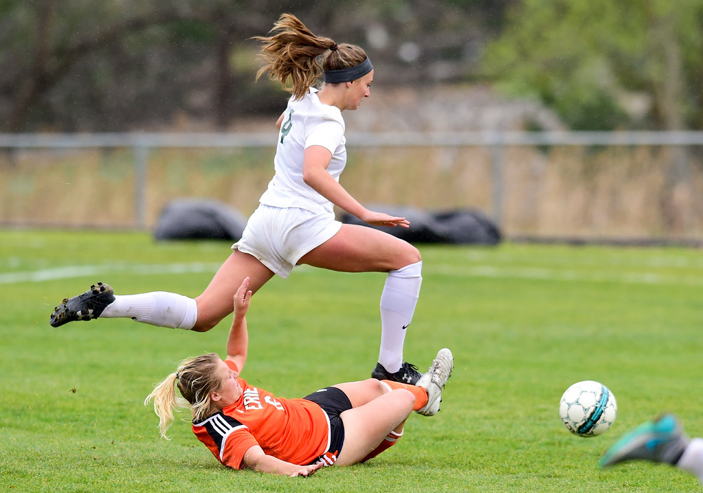 . Niwot High School\'s Madison Barkow (No. 4) tries to shake a slide tackle from Erie High School\'s Maddie Foster (No. 6) on Wednesday. More photos: BoCoPreps.com. Matthew Jonas/Staff Photographer May 10, 2017