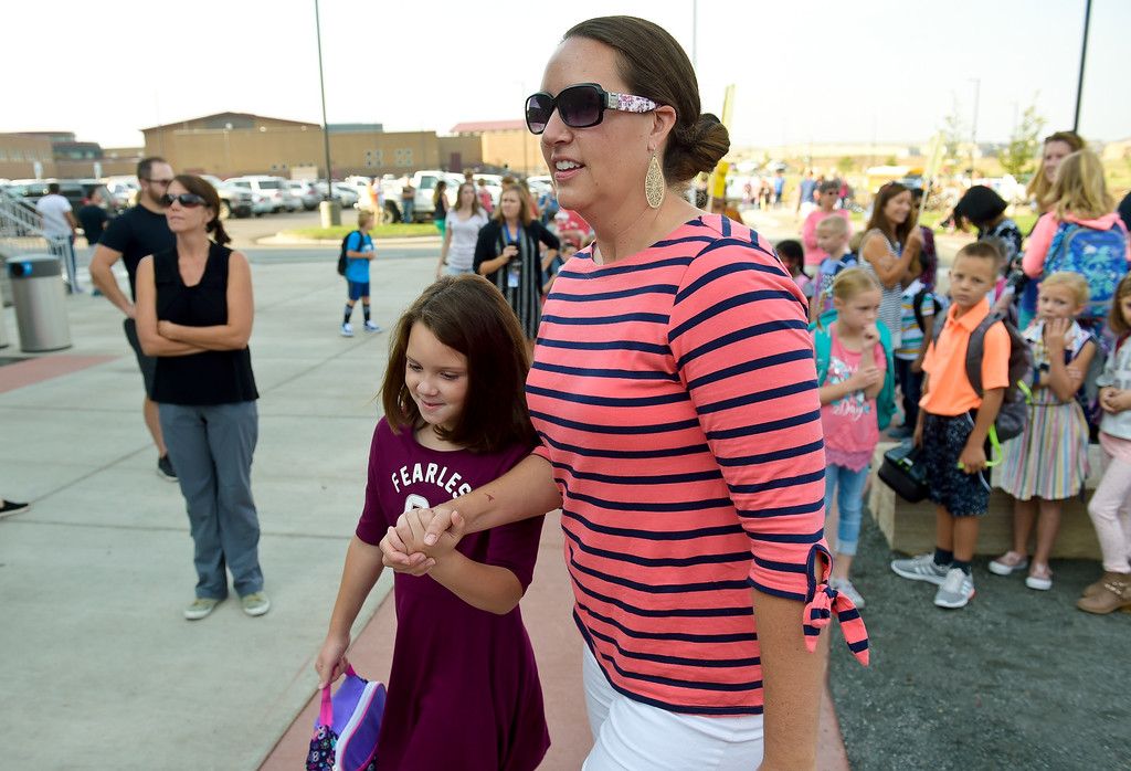 . ERIE, CO - AUG. 15: Michelle Chudleigh walks her daughter Charlotte, a second grader, to the entrance of Soaring Heights PK-8, 3280 County Road 5, on the first day of school Wednesday morning, Aug. 15, 2018. The new school has about 960 students enrolled. To view more photos visit timescall.com. (Photo by Lewis Geyer/Staff Photographer)