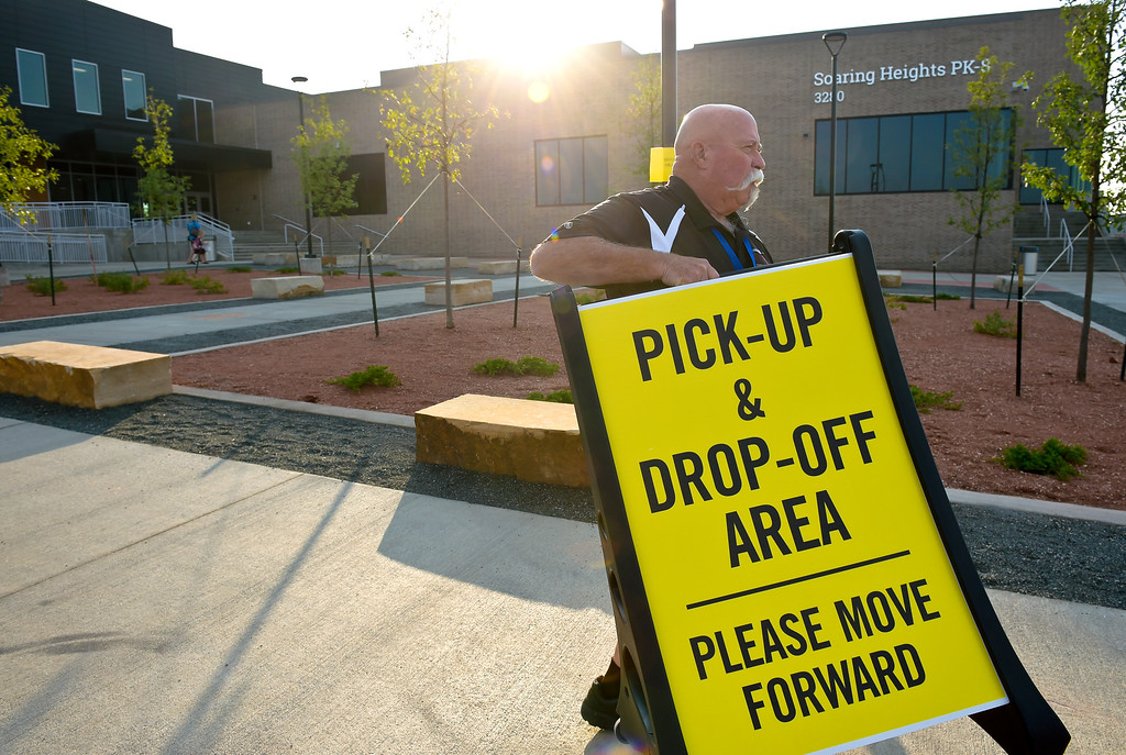 . ERIE, CO - AUG. 15: Campus supervisor Tom Billmaier places signs in front of Soaring Heights PK-8, 3280 County Road 5, on the first day of school Wednesday morning, Aug. 15, 2018. The new school has about 960 students enrolled. To view more photos visit timescall.com. (Photo by Lewis Geyer/Staff Photographer)
