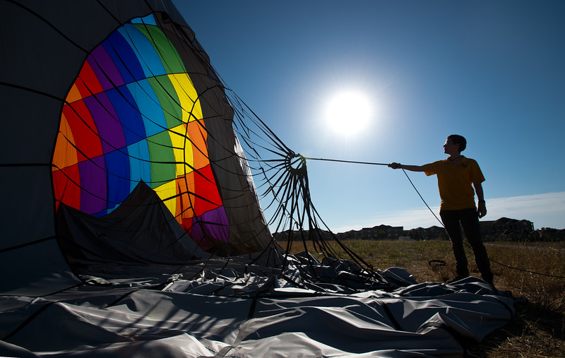 "Christina Longman, a crew member with Fair Winds Hot Air Balloon Flights, helps take down an air balloon after a morning launch from Lafayette on Friday.<br /> More photos:  <a href=""http://www.dailycamera.com"">http://www.dailycamera.com</a><br /> (Autumn Parry/Staff Photographer)<br /> July 8, 2016"