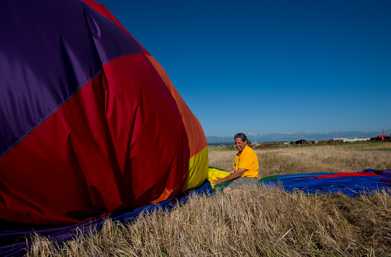 "Jeff Meeker, owner of Fair Winds Hot Air Balloon Flights, takes down an air balloon after a launch from Lafayette on Friday.<br /> More photos:  <a href=""http://www.dailycamera.com"">http://www.dailycamera.com</a><br /> (Autumn Parry/Staff Photographer)<br /> July 8, 2016"