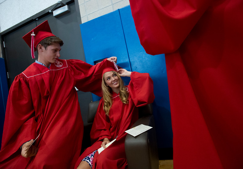 "Wyatt Dessel helps Olivia Kois adjust her tassel as they prepare for graduation prior to Fairview High School's commencement ceremony at 1st Bank Center in Broomfield on Sunday.<br /> More photos:  <a href=""http://www.dailycamera.com"">http://www.dailycamera.com</a><br /> Autumn Parry/Staff Photographer<br /> May 22, 2016"