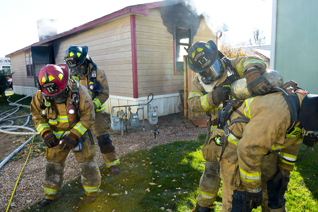 . LONGMONT, CO - NOVEMBER 9: Longmont firefighters have their air tanks replaced at the scene of a mobile home fire in the Weston Manor mobile home park, 729 17th Ave., Nov. 9, 2018. (Photo by Lewis Geyer/Staff Photographer)