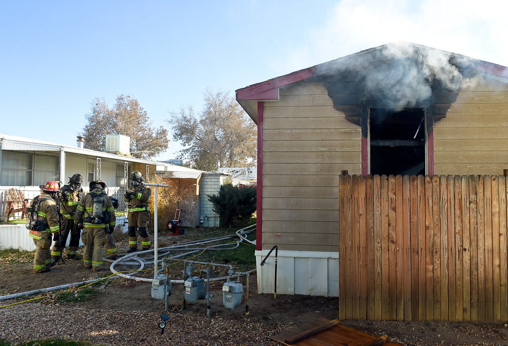 . LONGMONT, CO - NOVEMBER 9: After extinguishing the fire, Longmont firefighters gather next to a mobile home in the Weston Manor mobile home park, 729 17th Ave., Nov. 9, 2018. (Photo by Lewis Geyer/Staff Photographer)
