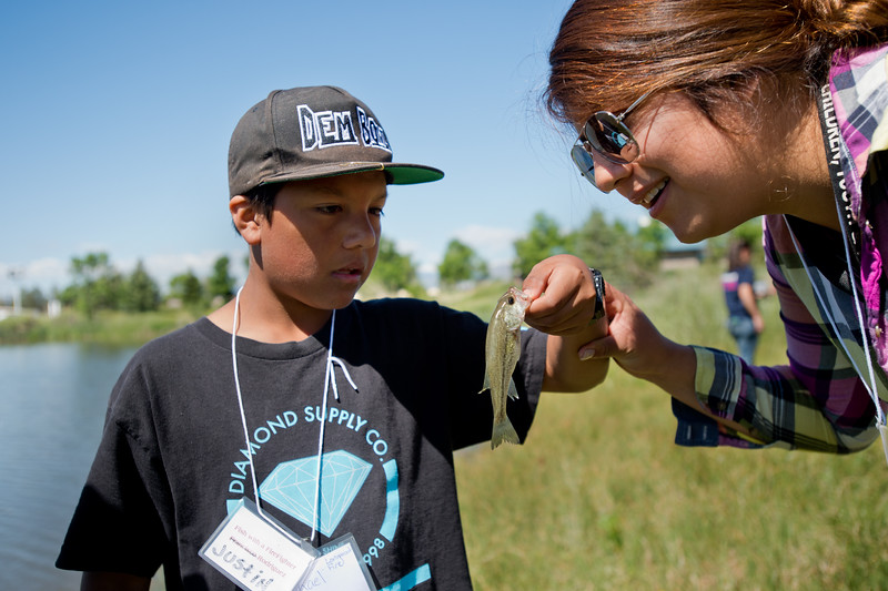 """Justin Rodriguez, 13, shows a small bass he caught to Lupita Crespo, a staff member with Children Youth and Families, during the first """"Fish with a Firefighter"""" event held by the Breakfast Optimists Club, city of Longmont, and Kids Fishing Incorporated, at Izaac Walton pond in Longmont on Saturday. <br /> More photos:  <a href=""""http://www.dailycamera.com"""">http://www.dailycamera.com</a><br /> (Autumn Parry/Staff Photographer)<br /> June 4, 2016"""