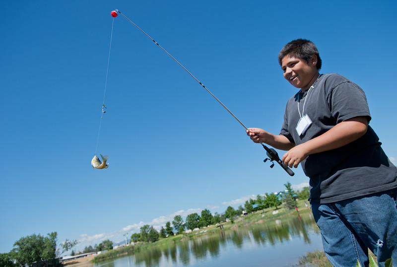 """Marc Rodriguez, 14, reels in a bluegill, which he caught while fishing with Lieutenant Brian Jackson, from the Longmont Fire Department, during the first """"Fish with a Firefighter"""" event held by the Breakfast Optimists Club, city of Longmont, and Kids Fishing Incorporated, at Izaac Walton pond in Longmont on Saturday.<br /> More photos:  <a href=""""http://www.dailycamera.com"""">http://www.dailycamera.com</a><br /> (Autumn Parry/Staff Photographer)<br /> June 4, 2016"""