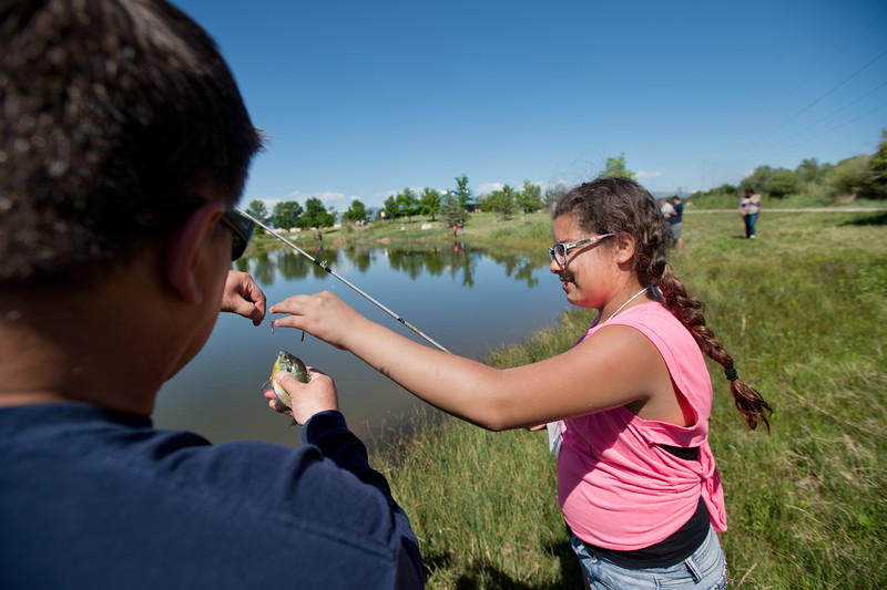 """Chief of Longmont Fire Department Jerrod Vanlandingham helps Giselle Pardo, 11, unhook a bluegill from her line during the first """"Fish with a Firefighter"""" event held by the Breakfast Optimists Club, city of Longmont, and Kids Fishing Incorporated, at Izaac Walton pond in Longmont on Saturday. <br /> More photos:  <a href=""""http://www.dailycamera.com"""">http://www.dailycamera.com</a><br /> (Autumn Parry/Staff Photographer)<br /> June 4, 2016"""