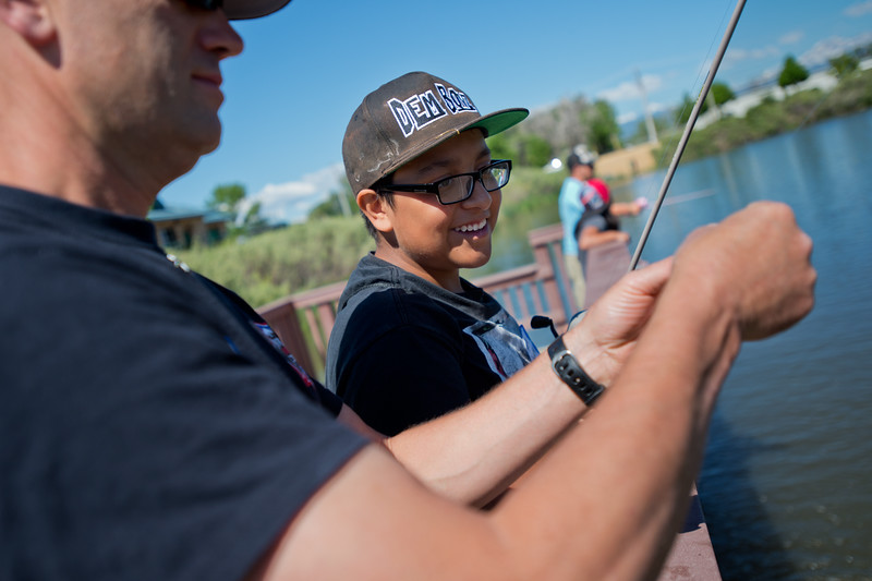 """Alex Cabrera, 13, and Joe Pendergast, a firefighter engineer with the Longmont Fire Department, change their lure during the """"Fish with a Firefighter"""" event held by the Breakfast Optimists Club, city of Longmont, and Kids Fishing Incorporated, at Izaac Walton pond in Longmont on Saturday. <br /> More photos:  <a href=""""http://www.dailycamera.com"""">http://www.dailycamera.com</a><br /> (Autumn Parry/Staff Photographer)<br /> June 4, 2016"""