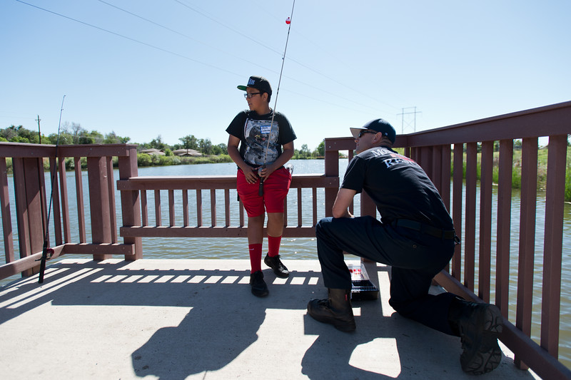 """Alex Cabrera, 13, and Joe Pendergast, a firefighter engineer with the Longmont Fire Department, discuss the best lure to use during the first """"Fish with a Firefighter"""" event held by the Breakfast Optimists Club, city of Longmont, and Kids Fishing Incorporated, at Izaac Walton pond in Longmont on Saturday. <br /> More photos:  <a href=""""http://www.dailycamera.com"""">http://www.dailycamera.com</a><br /> (Autumn Parry/Staff Photographer)<br /> June 4, 2016"""