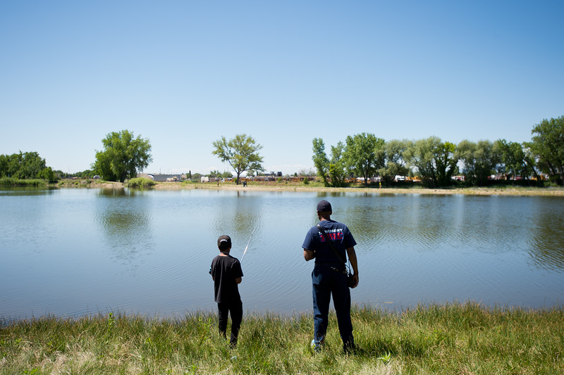 """Justin Rodriguez, 13, fishes with Lieutenant Michael Major, from the Longmont Fire Department, during the first """"Fish with a Firefighter"""" event held by the Breakfast Optimists Club, city of Longmont, and Kids Fishing Incorporated, at Izaac Walton pond in Longmont on Saturday. Rodriguez caught a small bass which he used as bait to try and catch a bigger fish. <br /> More photos:  <a href=""""http://www.dailycamera.com"""">http://www.dailycamera.com</a><br /> (Autumn Parry/Staff Photographer)<br /> June 4, 2016"""