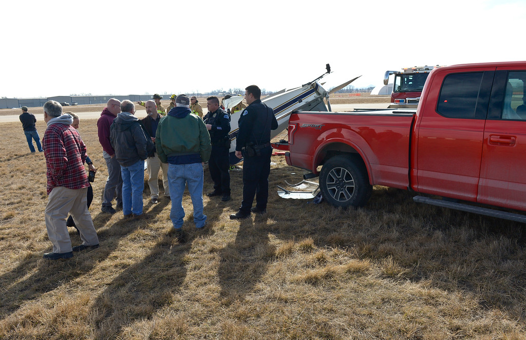 . Longmont police talk with airport personnel after a plane flipped onto its roof at Vance Brand Municipal Airport Friday afternoon. To view more photos and a video visit timescall.com. Lewis Geyer/Staff Photographer Feb. 16, 2018