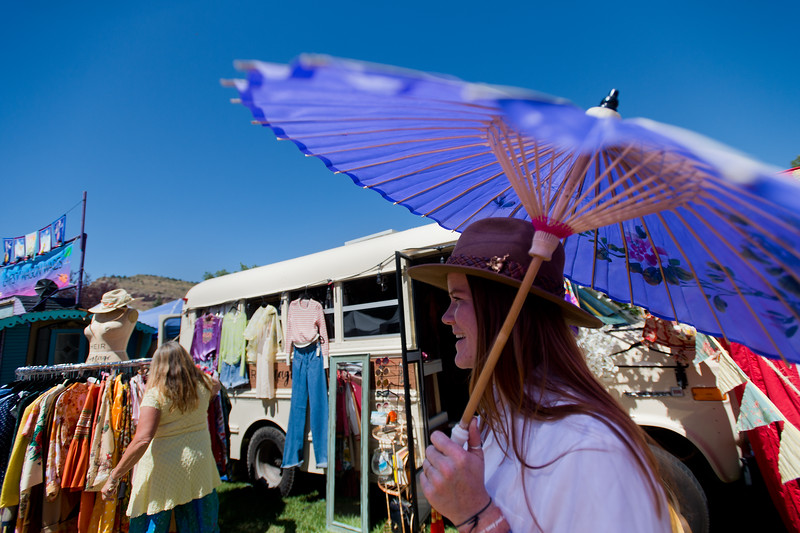 "Kelsey McCartney, co-creator of Heir Vintage, shades herself from the sun as festival-goers look through their clothing during the Folks Fest in Lyons on Sunday. <br /> More photos:  <a href=""http://www.dailycamera.com"">http://www.dailycamera.com</a><br /> (Autumn Parry/Staff Photographer)<br /> August 21, 2016"