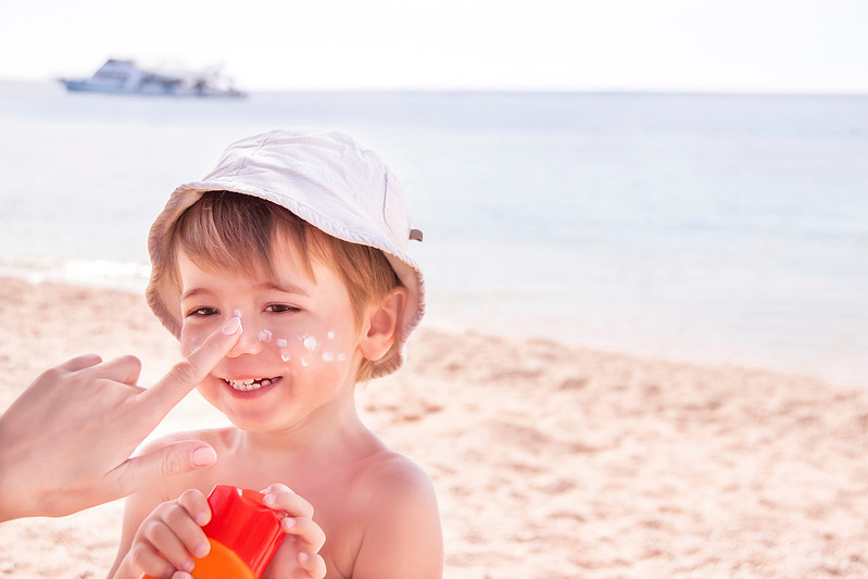 Hand of caucasian mother applying suncream  to her son on beach.