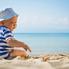 Baby boy with hat sitting on the beach.