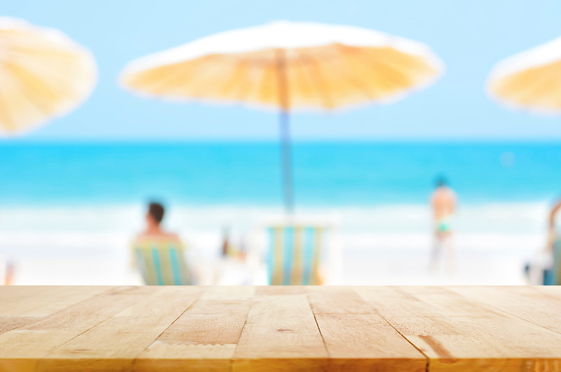 Wood table top on blurred blue sea and white sand beach background with some people