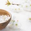 Floating flowers ( Cherry blossom) in white bowl. Focus on near flower