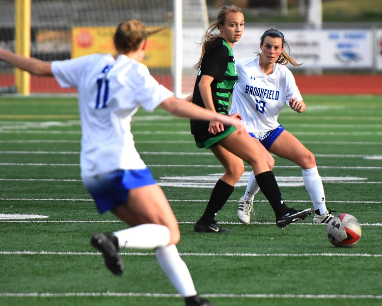 Broomfield's Jessie Mooney watches a pass to teammate Ashley Tuccio during the Eagles' game against Fossil Ridge on Tuesday, April 10, at Broomfield High School.