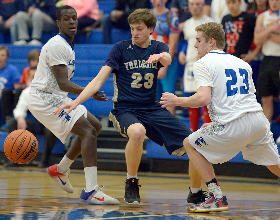 . Frederick\'s Kyle Lahr goes after the ball between Longmont\'s Tol Mugunga, left, and Caden Dion in the first quarter Wednesday night at Longmont High School. To view more photos visit bocopreps.com. Lewis Geyer/Staff Photographer Feb. 22, 2017