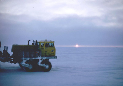 A Rolligon driving softly across the snow-covered tundra, with the midnight sun as its backdrop.