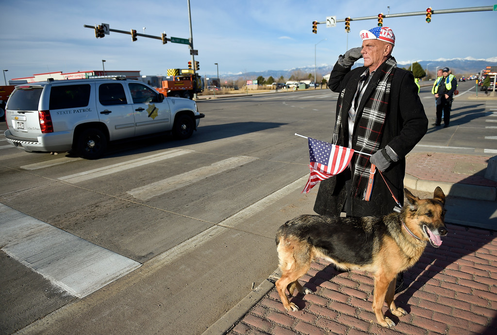 . LONGMONT, CO - MARCH 21: Patrick McFarlane and his dog Athena stand at Main Street and Colo. 66 fo the funeral procession of Colorado State Patrol Cpl. Daniel Groves March 21, 2019. Groves was struck by a vehicle while assisting a motorist on I-76 during last week\'s blizzard. To view more photos visit timescall.com. (Photo by Lewis Geyer/Staff Photographer)