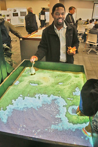 Geographic Information Systems Professor David Gwenzi manipulates an augmented reality sandbox in the Humboldt State University Library on Wednesday. The sandbox was part of GIS Day at the university. The event also featured speakers, a jumbo map display, free pizza, and a student map and poster competition and gallery. (Shaun Walker -- The Times-Standard)