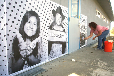 "Parent volunteer Kathy Jauernig pastes up a giant poster of a student at South Bay School on Thursday afternoon. As a Turnaround Arts partner, the school hosted Inside Out Project's photobooth truck and about 100 photos were taken of students and staff, which were then printed as giant black and white posters almost instantly. Many were then pasted onto school buildings as a giant mural. The project was meant to make a ""bold, visual statement about the school's commitment to leveraging the arts for educational equity."" (Shaun Walker -- The Times-Standard)"