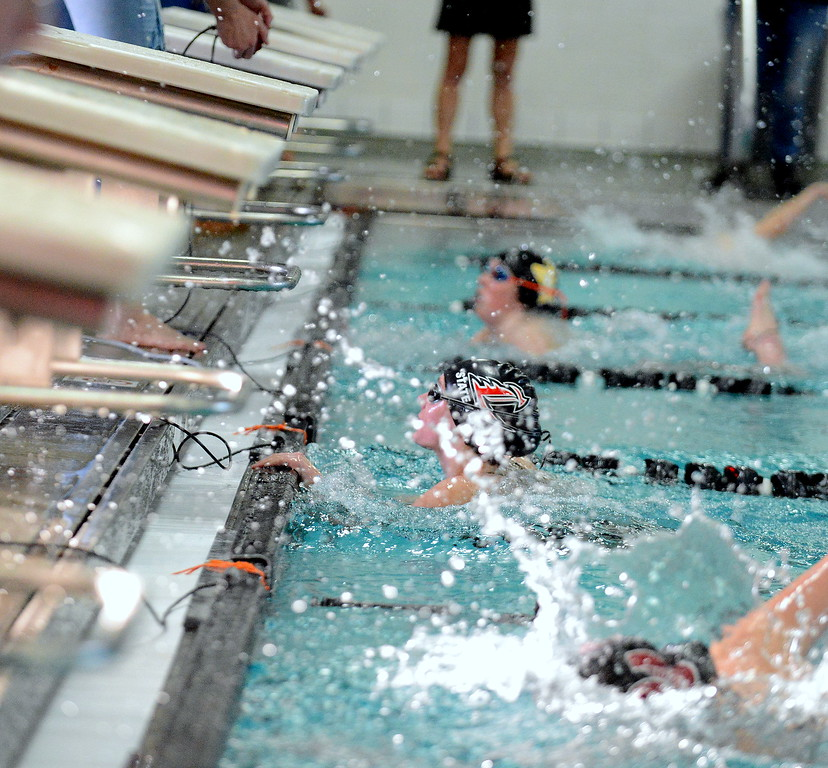 . Loveland\'s Ashley Peet (center) looks up at the board for her winning tim in the 50-yard freestyle at Friday\'s District Championships at the Mountain View Aquatic Center. (Mike Brohard/Loveland Reporter-Herald)