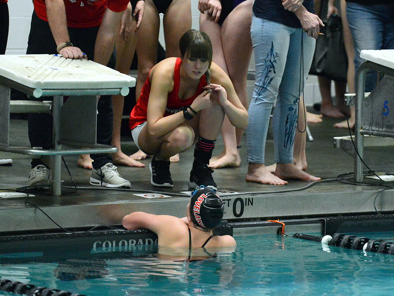 Loveland coach Sarah Vlatkovich talks with Delaney McNally after she won the 500-yard freestyle at Friday's District Championships at the Mountain View Aquatic Center. There was a bit of confusion on the number of laps McNally swam, an issue created by the officials. (Mike Brohard/Loveland Reporter-Herald)