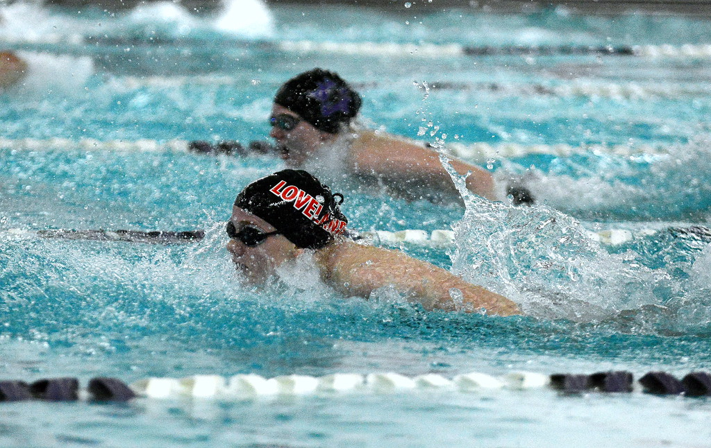 . Sisters compete side by side as Loveland\'s Jordan Reichhardt surges ahead of Tasha Reichhardt of Mountain View on her way to winning the 100-yard butterfly at Friday\'s District Championships at the Mountain View Aquatic Center. (Mike Brohard/Loveland Reporter-Herald)