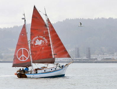The Golden Rule, a historic anti-nuclear peace boat, passes the former King Salmon nuclear power plant, background, while Humboldt Bay on Wednesday morning. (Shaun Walker — The Times-Standard)