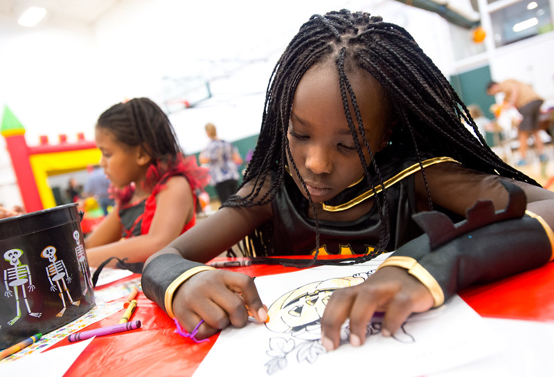"""Claire Peter-Bettel, 8, colors a picture of a pumpkin during the Halloween Carnival at the South Boulder Recreation Center on Friday.<br /> More photos:  <a href=""""http://www.dailycamera.com"""">http://www.dailycamera.com</a><br /> (Autumn Parry/Staff Photographer)<br /> October 28, 2016"""