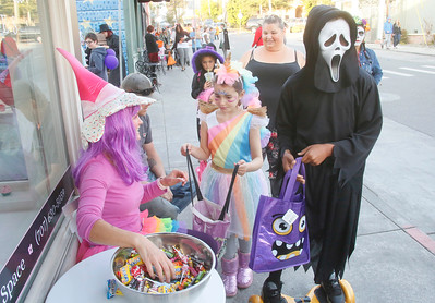"Bonnie Debord of Mia Bella Cupcakes, left, gives candy to Sol Coradines, 6, of McKinleyville and Garron Turner, 11, of Arcata during Halloween on the Plaza on Wednesday night. The event also featured ""Thriller"" dances, fire trucks, the Marching Lumberjacks, music, and a carved pumpkin contest. (Shaun Walker -- The Times-Standard)"