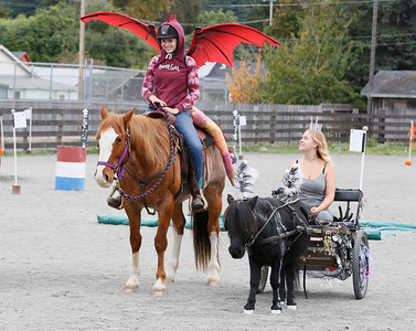 Arianna Williams of Fortuna, left, rides Sugar Man as Mistea Cardelli of Arcata gets pulled by Enderman at the Haunted Horse event in the Blue Lake Arena on Saturday. The event, with about 21 riders, featured children, adults, and horses dressed up, an obstacle course, candy and prizes. (Shaun Walker -- The Times-Standard)