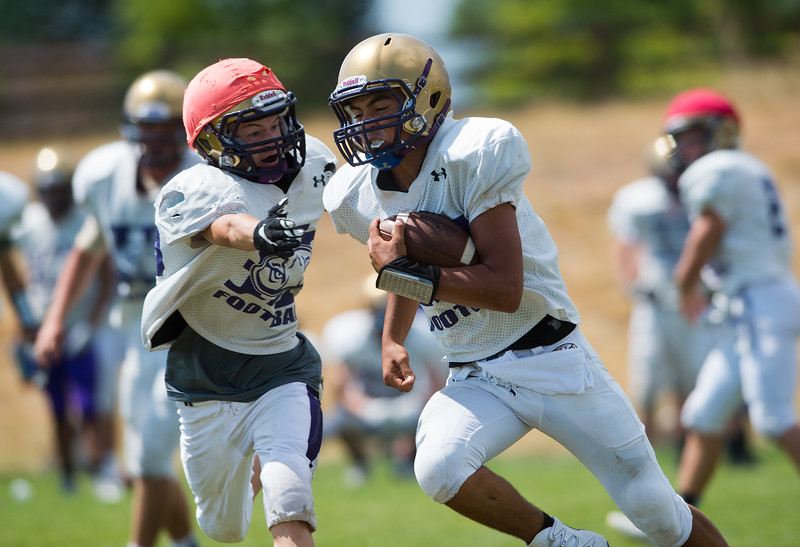 """Stone Samaras (right) dodges defense during a drill at football practice at Holy Family High School in Broomfield on Friday.<br /> More photos:  <a href=""""http://www.BoCoPreps.com"""">http://www.BoCoPreps.com</a><br /> (Autumn Parry/Staff Photographer)<br /> August 19, 2016"""