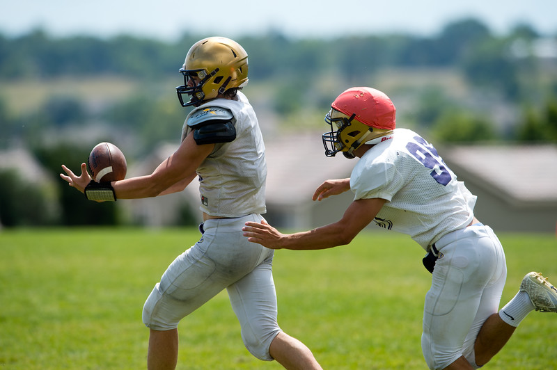 """Joe Golter (right) tries to grab the ball from Kyle Helbig during football practice at Holy Family High School in Broomfield on Friday. <br /> More photos:  <a href=""""http://www.BoCoPreps.com"""">http://www.BoCoPreps.com</a><br /> (Autumn Parry/Staff Photographer)<br /> August 19, 2016"""