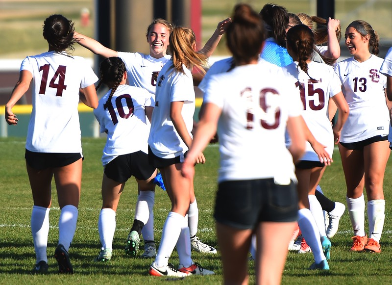 The Silver Creek girls soccer team rushes onto the field to congratulate Kate Eggen on her golden goal that ended the game between No. 2 Silver Creek and No. 10 Holy Family on Friday, April 27, at Silver Creek High School in Longmont.