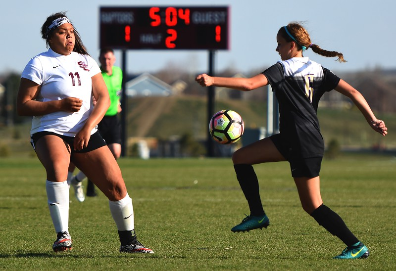 Holy Family's Kacy Clements (right) tries to control the ball while Silver Creek's Margaret Goldsberry defends during the game between No. 2 Silver Creek and No. 10 Holy Family on Friday, April 27, at Silver Creek High School in Longmont.