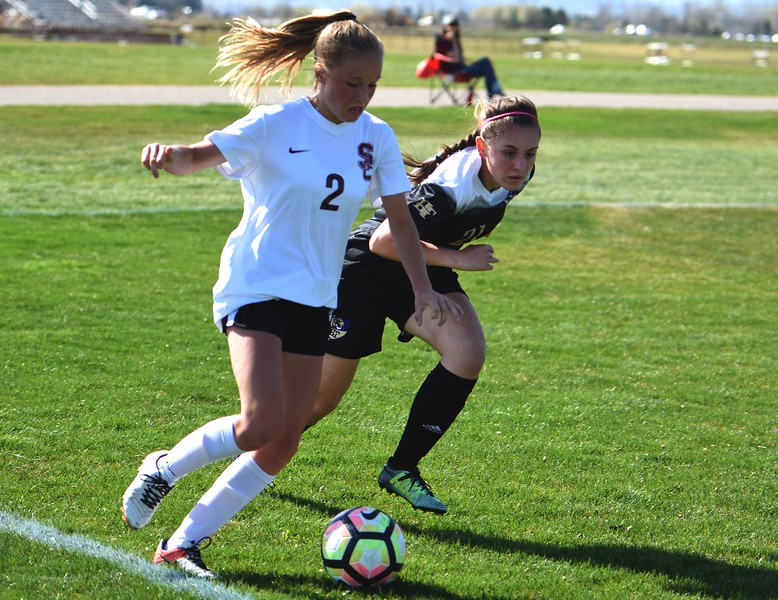 Silver Creek's Annika Kassenbrock (left) toes the end line while Holy Family's Kaitlin Rentmeester defends during the game between No. 2 Silver Creek and No. 10 Holy Family on Friday, April 27, at Silver Creek High School in Longmont.
