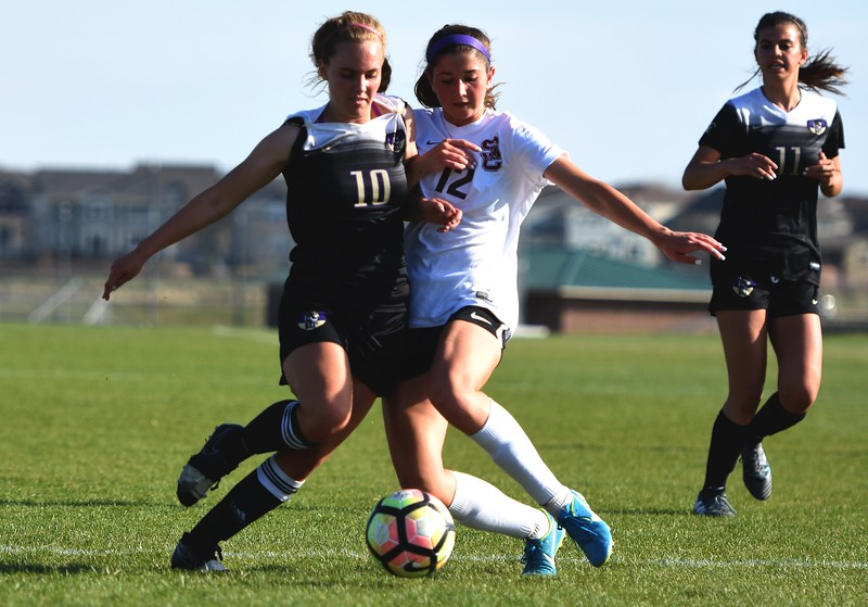 Holy Family's Kody Clements (left) and Silver Creek's Alexa Karsel fight for a loose ball during the game between No. 2 Silver Creek and No. 10 Holy Family on Friday, April 27, at Silver Creek High School in Longmont.