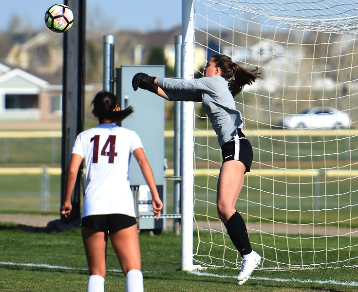 Silver Creek keeper Kaeyla Noble makes a leaping save during the game between No. 2 Silver Creek and No. 10 Holy Family on Friday, April 27, at Silver Creek High School in Longmont.