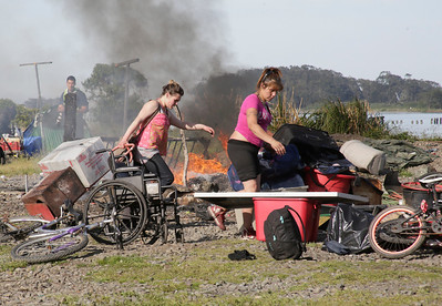 Shaun Walker — The Times-Standard  Two women prepare to leave their site as a campsite burns behind them.