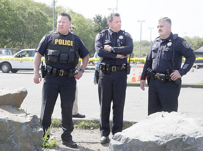 Shaun Walker — The Times-Standard  Eureka Police Chief Andrew Mills, center, and captains Steve Watson, left, and Brian Stephens discuss the ongoing operation near the Bayshore Mall parking lot.