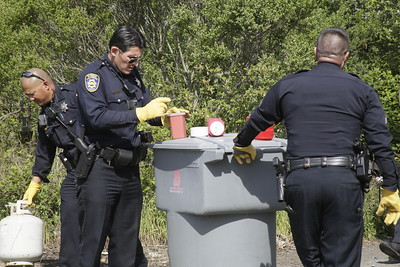 Shaun Walker — The Times-Standard  Eureka Police officers dispose of hypodermic needles and propane containers from one campsite.
