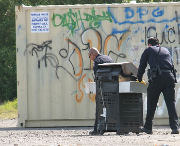 Shaun Walker — The Times-Standard  Two EPD officers roll what was reportedly a barbecue grill with partly burned stolen identification cards in it toward an on-site storage container.