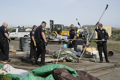 Shaun Walker — The Times-Standard  Eureka Police officers dismantle a tent that sat on wooden pallets.