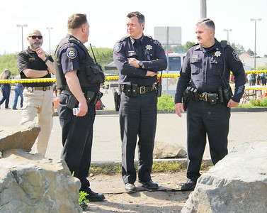 Shaun Walker — The Times-Standard  Eureka Police Chief Andrew Mills, center, and captains Steve Watson, left, and Brian Stephens, right, and Humboldt County Sheriff's Master Chaplain Andrew Broese Van Groenou discuss the ongoing operation near the Bayshore Mall parking lot.