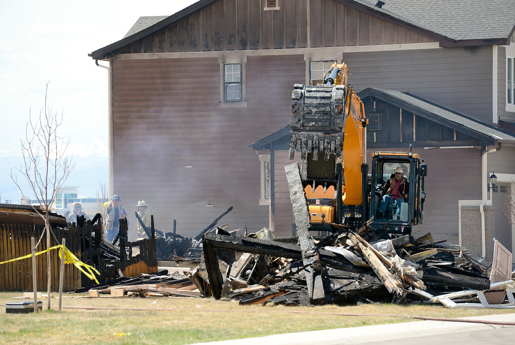. Investigators stand by as a track hoe works to remove debris from the burned remains of a house on the 6300 Block of Twilight Avenue in Firestone on Tuesday. More photos: TimesCall.com. Matthew Jonas/Staff Photographer April 18,  2017