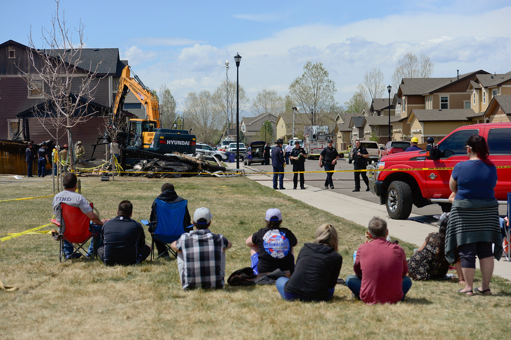 . A group of people watch as track hoe works to remove debris from the burned remains of a house on the 6300 Block of Twilight Avenue in Firestone on Tuesday. More photos: TimesCall.com. Matthew Jonas/Staff Photographer April 18,  2017