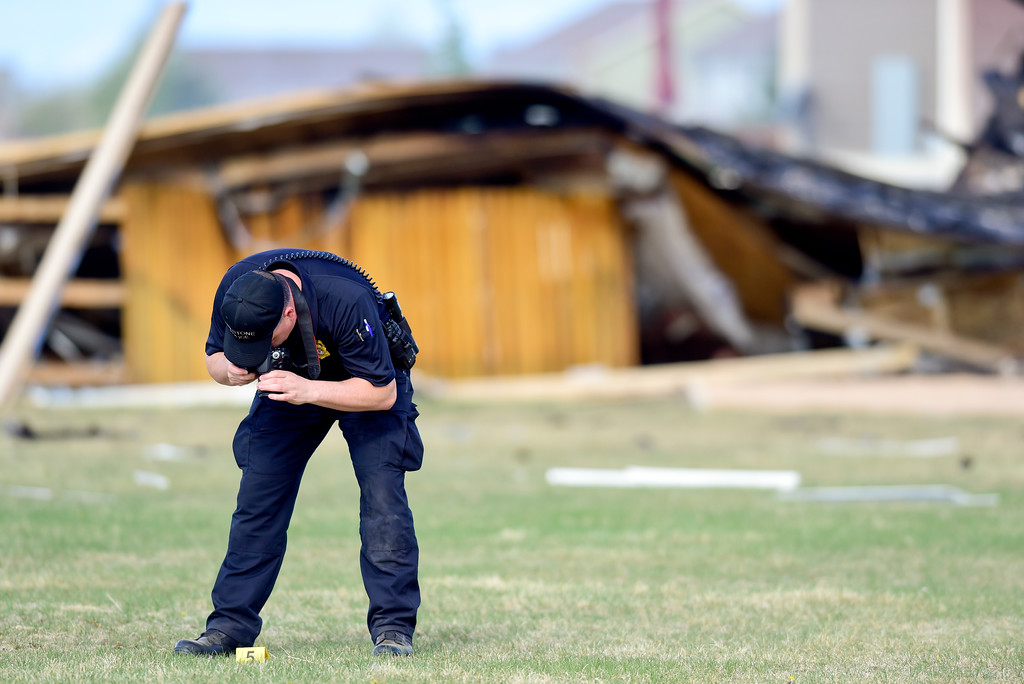 . An investigator with the Firestone Police photographs evidence markers on debris that came from a house on Tuesday. More photos: TimesCall.com. Matthew Jonas/Staff Photographer April 18,  2017