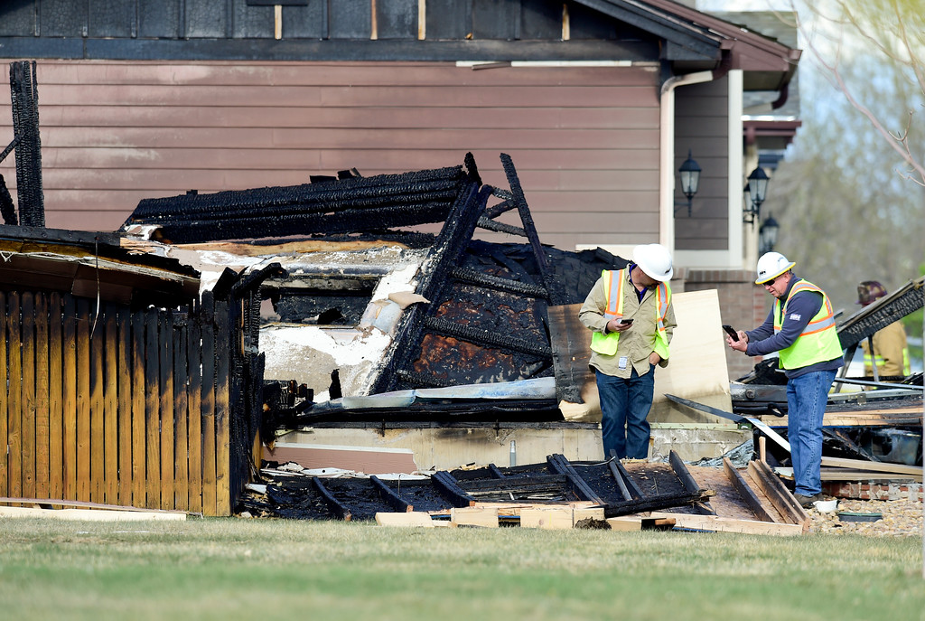 . Black Hills Energy workers are seen near a burned house on Tuesday. More photos: TimesCall.com. Matthew Jonas/Staff Photographer April 18,  2017